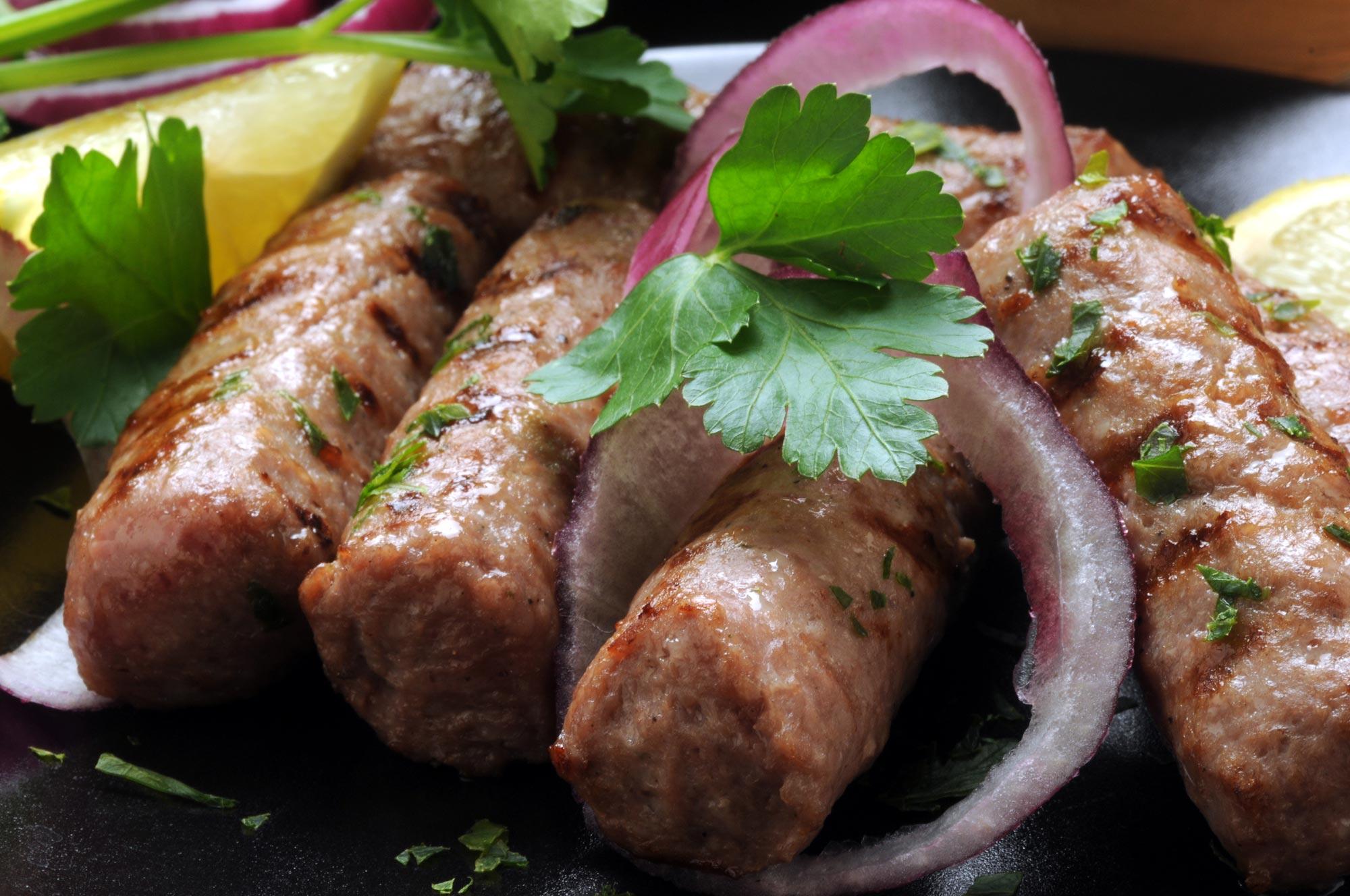 Cevapcici serveret med bønnesalat vendt i salsa verte